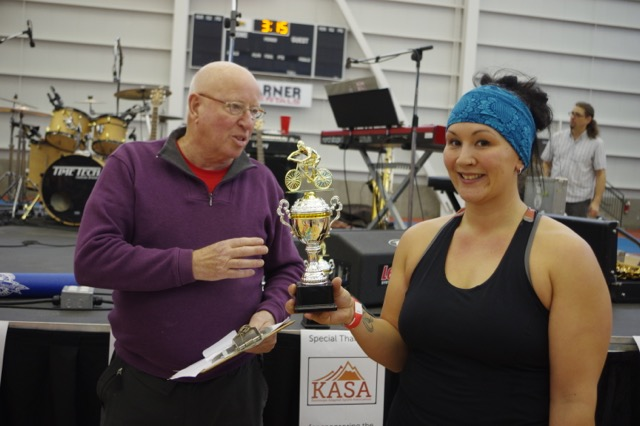 Women's roller racing derby winner Tami Newman (right) accepts her trophy from IGCC board member John Tilley at the Kamloops Indoor Gran Fondo.